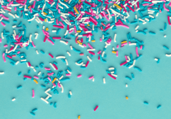 Lots of multicoloured sprinkles on a bright blue background