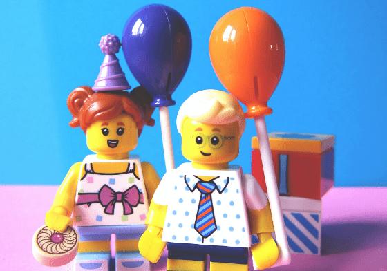 Two lego pieces holding lego balloons
