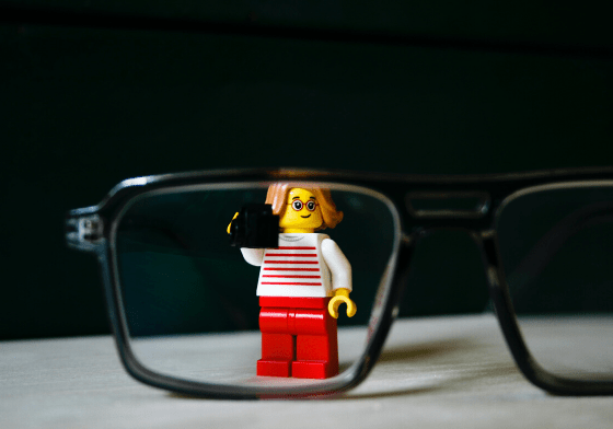 A lego woman standing behind the lens of a pair of glasses