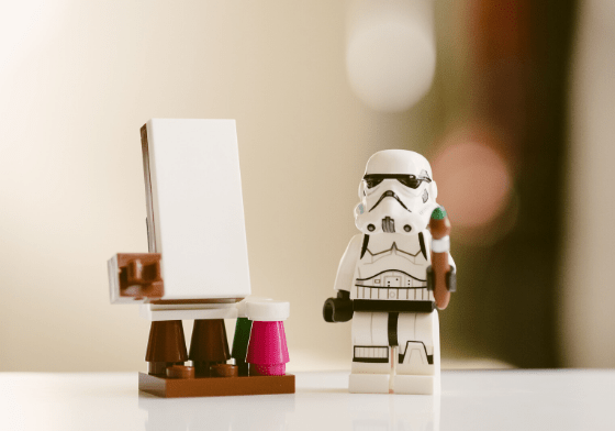 A lego stormtrooper holding a lego paintbrush and standing next to a lego easel