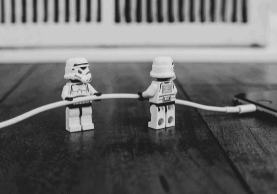 Two lego storm troopers plugging a cable into a mobile phone