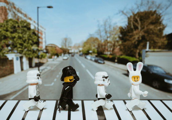 A replication of the famous Beatles album cover with two lego storm troopers, a lego Darth Vader and a lego man in a bunny costume crossing the road.