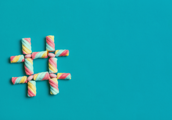 A blue background with sweets arranged in the shape of a hashtag