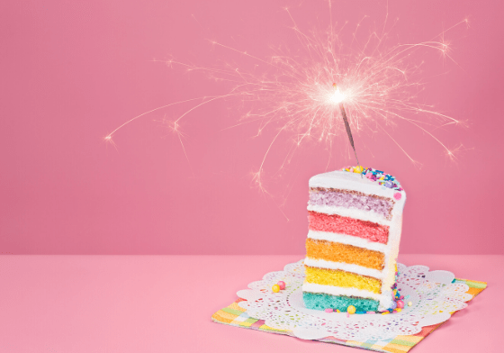 A bright pink background with a piece of cake. The cake has five different colour layers and has a sparkler sticking out the top.